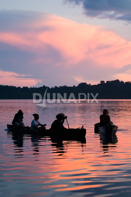 Women paddle home to Kia village at sunset. They have been collecting oysters in preparation for a funeral feast.