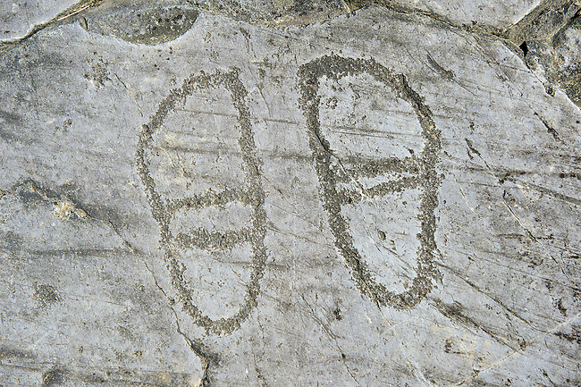 Petroglyph, rock carving, of two feet outlines. Carved by the ancient Camuni people in the iron age between 1000-1600 BC. Rock no 24,  Foppi di Nadro, Riserva Naturale Incisioni Rupestri di Ceto, Cimbergo e Paspardo, Capo di Ponti, Valcamonica (Val Camonica), Lombardy plain, Italy