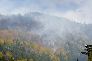 Black Hawk helicopter dropping water on a forest fire on Dilly Cliff in Kinsman Notch, New Hampshire in October 2017. These cliffs are located behind the Lost River Gorge and Boulder Caves on Route 112 in North Woodstock.