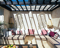 Piled high with scatter cushions the banquette sofas on the covered terrace have been constructed from raw plaster in traditional Moroccan style