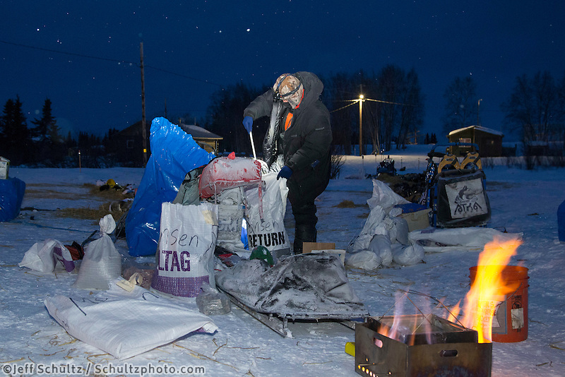 Lars Monsen prepares to cook dog food in the early morning at the Kaltag checkpoint in on Sunday March 13th during the 2016 Iditarod.  Alaska    <br /> <br /> Photo by Jeff Schultz (C) 2016  ALL RIGHTS RESERVED