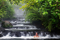 A visitor (mr) enjoys one of the warm streams that flows through Tabacon Hot Spring Resort and Spa, Costa Rica