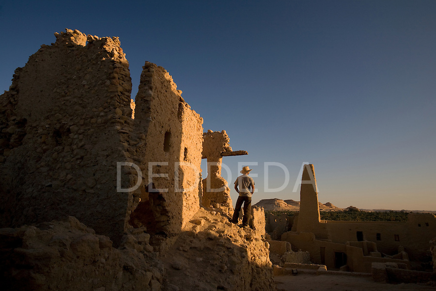 A male tourist stands within the Temple of the Oracle, dedicated to Amun, which was built in the 6th century BC, and is one of the most revered oracles in the ancient Mediterranean. The Temple sits in the ruins of Aghurmi village in the Siwa Oasis, Egypt. Alexander the Great consulted the priests of Amun at the Temple of the Oracle in 331 BC.