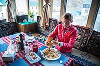 Inside a Gokyo lodge while on a trail running tour, having breakfast before starting up Renjo La Pass, the third pass of the 3 Passes Tour, Khumbu Valley, Nepal.