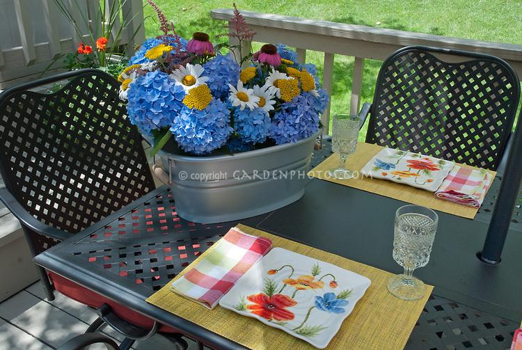 Hydrangea, daisy Leucanthemum, Achillea yarrow, Echinacea purple coneflower, Astilbe, cut flowers in galvanized container on patio table in backyard deck