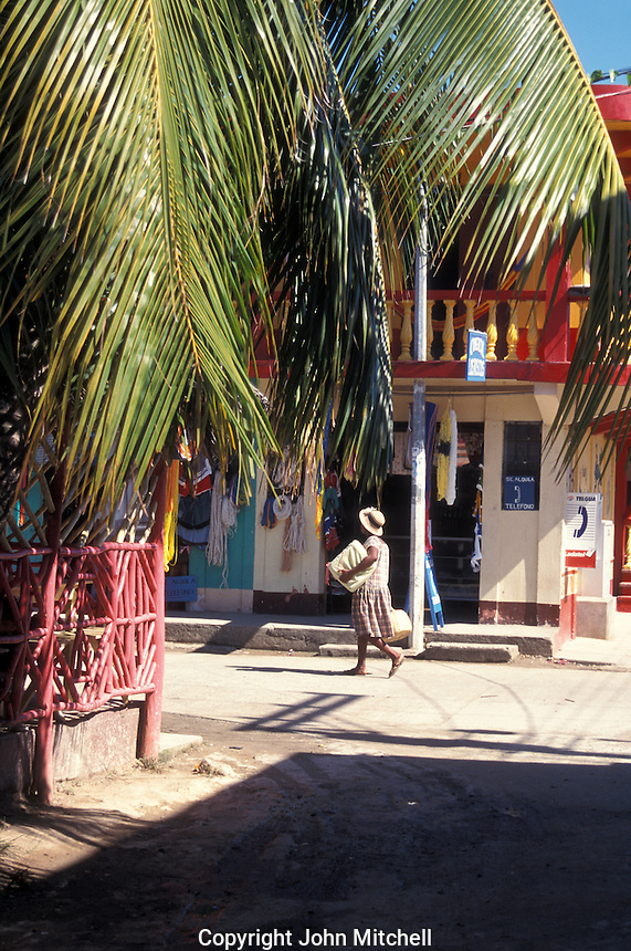 Black woman walking down a street in the town of Livingston on the Caribbean coast of Guatemala