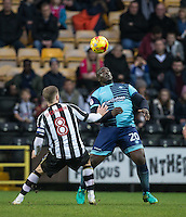 Adebayo Akinfenwa of Wycombe Wanderers controls the ball under pressure from Michael O'Connor of Notts Co during the Sky Bet League 2 match between Notts County and Wycombe Wanderers at Meadow Lane, Nottingham, England on 10 December 2016. Photo by Andy Rowland.