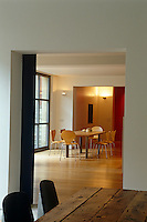 View from the end of the rough wooden table in the dining room into the kitchen area