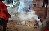 A man and his child sleep inside a mosquito net in a relief shelter in Mullaittivu, near where the tsunami struck in the northeastern coast of Sri Lanka, an area ravaged also by civil war. .The December 26, 2004 tsunami killed around 40,000 people along Sri Lanka's southern, eastern and northern shores, tearing thousands of families apart. .The bulk of the dead were women and children - husbands lost young brides and around 4,000 children lost one or both parents. .Even before the tsunami struck, people here in the northeast had already been displaced four times by the Tigers' two-decade war for autonomy. .In some places, the scars of war and the tsunami have become one. Remnants of walls torn down by waves are pockmarked with bullet holes and shrapnel from shells fired before a 2002 ceasefire plunged a civil war that killed over 64,000 people into limbo. ..Picture taken March 2005 by Justin Jin