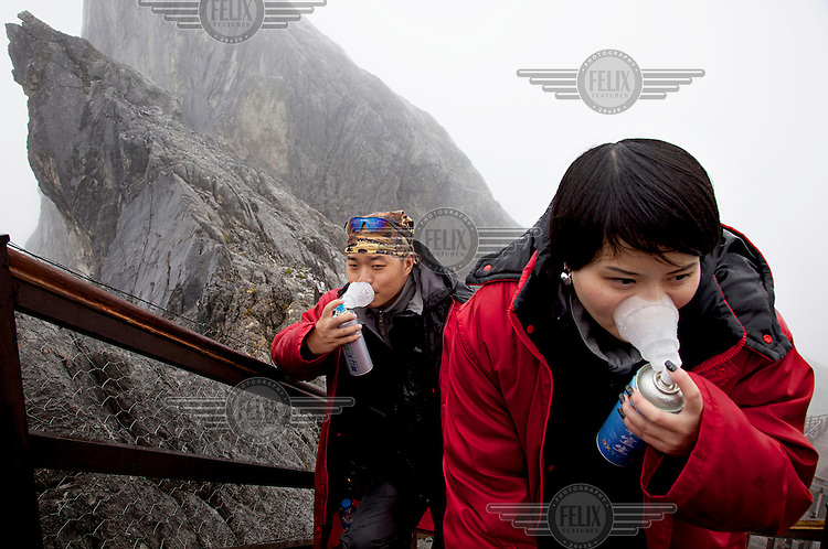 Visitors reach out for their oxygen tanks on the ascent to the 4300 metre shoulder of Yulong Mountain near the ancient town of Lijiang. /Felix Features