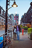 CANADA, Vancouver, British Columbia, a couple stands on the street at dusk near the Blue Water Cafe and Raw Bar in Yaletown