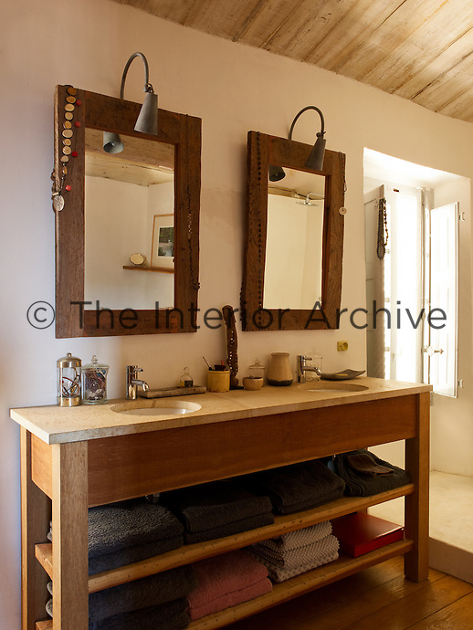 This twin basin unit has a marble surface on a wooden structure matched by the two mirrors hanging above it