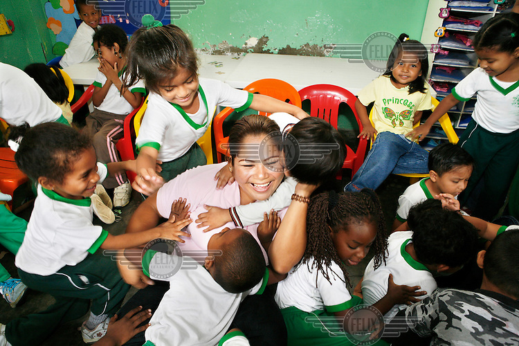 A teacher is hugged and mobbed by laughing children at the Los Amiguitos de Membol, a nursery school in a poor neighbourhood of  Guayaquil, Ecuador's largest city. The school aims to give an education to the children of the city's barrios.