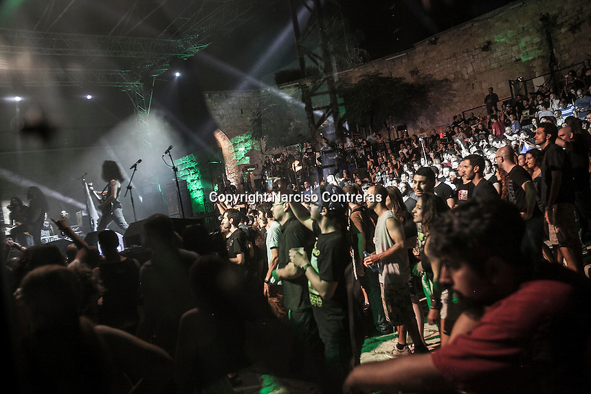 August 27, 2014 - Binyamina, Haifa District, Israel: Cem (left) Uri (centre) and Idan (right), guitar player, bass player and guitar player at Orphaned Land heavy metal band, are seen reflected in a safety glass as they perform a concert in Binyamina Amphitheatre at north of Israel. Orphaned Land is a music band founded by Jewish and Arabian musicians who combine ethnic music with rock metal as they recite verses in Hebrew and Arabic from the sacred Quram and Tora Scriptures. (Narciso Contreras/Polaris)