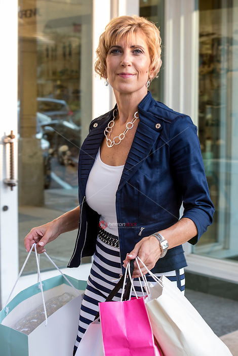 Closeup of a beautiful sexy woman who shops and holds bags at an outdoor shopping mall in Austin, Texas.