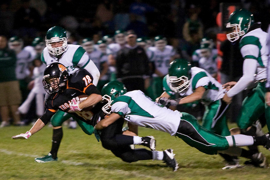 Post Falls Trojans junior running back Tyson Johnson attemps to evade a tackle during a local 5A game against the East Valley Knights in Post Falls, ID on Friday night. ..(Matt Mills McKnight for The Spokesman-Review).
