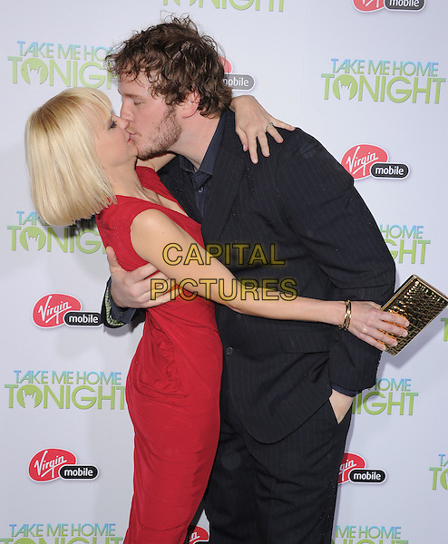 "ANNA FARIS & CHRIS PRATT .attends the Relativity Media's L.A. Premiere of ""Take Me Home Tonight"" held at The Regal Cinemas L.A. Live Stadium 14 in Los Angeles, California, USA, March 2nd, 2011..half length red sleeveless dress black shirt husband wife couple kissing kiss    suit                                                                  .CAP/RKE/DVS.©DVS/RockinExposures/Capital Pictures."