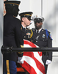 A Baltimore City police officer salutes as the casket of William Donald Schaefer is carried into the Statehouse.