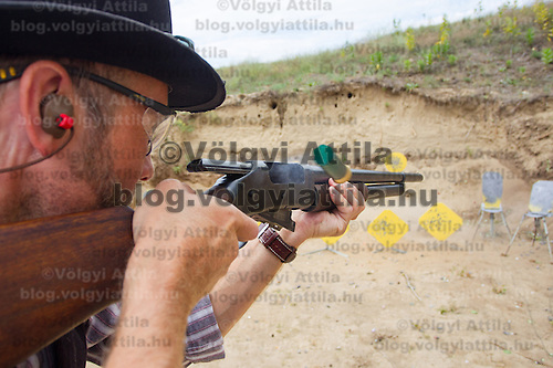 Participant fires his weapon during the Cowboy Action Shooting European Championship in Dabas, Hungary on August 11, 2012. ATTILA VOLGYI