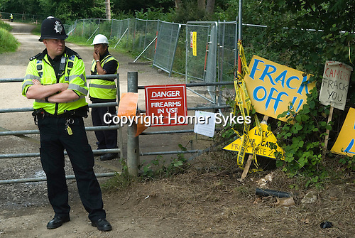 "Balcombe West Sussex UK. Police ans security guards, guard the Cuadrilla Resources site entrance, where Fracking is planned. The sign ""Danger Fire Arms in Use"", refers to game shooting on the Balcombe Estate."