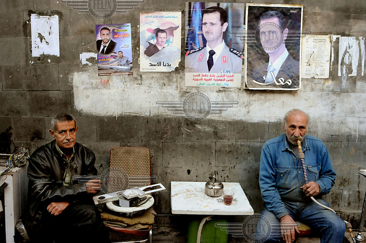 Portraits of president Bashar al-Assad adorn building walls in the city centre. Beneath them a man smokes a shisha (sheesha, narghile, hookah).