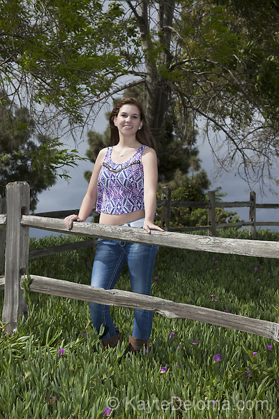 Portrait of a teenage girl in jeans and a crop top leaning on a wooden fence