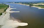 Foto: VidiPhoto<br /> <br /> DODEWAARD  - De drukst bevaarde rivier van Europa, De Waal, is door de langdurige droogte maandag geslonken tot een smalle stroom. Recre&euml;rende jonge koeien op de inmiddels brede stranden, kunnen haast naar de passerende schepen toe lopen. Binnenvaarders kunnen door de verminderde diepgang nu minder lading meenemen en het water blijft voorlopig dalen. Door de droogte is de waterstand in de grote rivieren zo laag, dat de kribben weer zichtbaar zijn. Die werden in het kader van Ruimte voor de Rivieren verlaagd en zitten normaal gesproken onder water. Rijkswaterstaat heeft code geel afgegeven vanwege die lage waterstand. Voor delen van de de Leidsche Rijn geldt inmiddels een vaarverbod en bij vrijwel alle sluizen nemen de wachttijden door de verminderde diepgang toe.