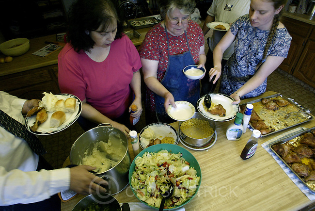 Salt Lake City,Utah--6/12/2005- .**ZONES**.FROM LEFT: Hal, Debbi, LeAnne and Amy Rushton serve a dinner of salad, corn, chicken, mashed potatoes and broccoli Sunday evening.  The family gathers together every Sunday...Photo By: Chris Detrick /Salt Lake Tribune.