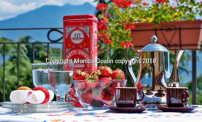 A bowl of fruit, strawberries, coffee and ice water on a terrace in Menaggio on Lake Como, Italy