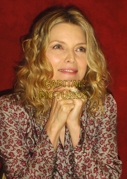 """MICHELLE PFEIFFER.Photocall for the film """"Cheri"""" at the Four Season, Wetherly Room, Los Angeles, California, USA..April 16th, 2009.half length grey gray red pattern wrap hand silver ring burgundy                              .CAP/AW.©Anita Weber/Capital Pictures."""