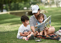 Fennalia Carle of Bentonville (center), reads to her kids Oliver Carle, 4, (from left) and Alison Carle, 1, Monday, July 27, 2020 at Gibson Park in Bentonville. Nataliya Chapovska and Fennalia Carle find a new park for their kids to visit every day. Carle likes Gibson Park because they have shade in the mornings, the time when they like to meet. Gibson Check out nwaonline.com/200728Daily/ for today's photo gallery. <br /> (NWA Democrat-Gazette/Charlie Kaijo)