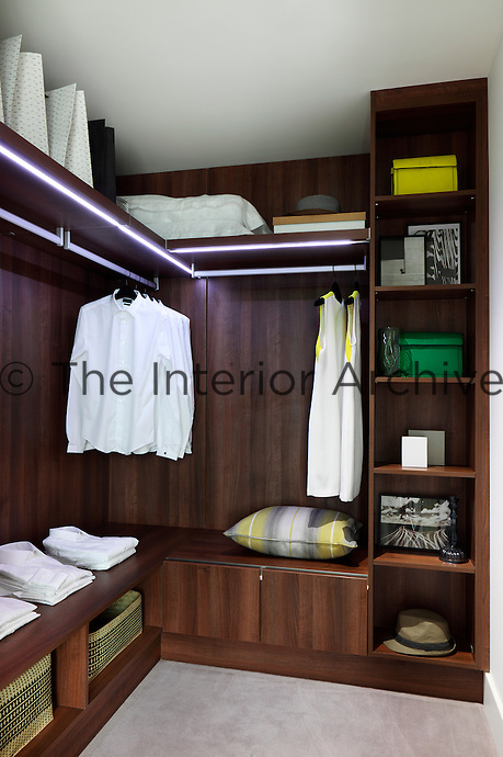 A wooden built in shelving unit in the corner of a bedroom with wicker baskets for storage and neatly folded clothes and hanging shirts.