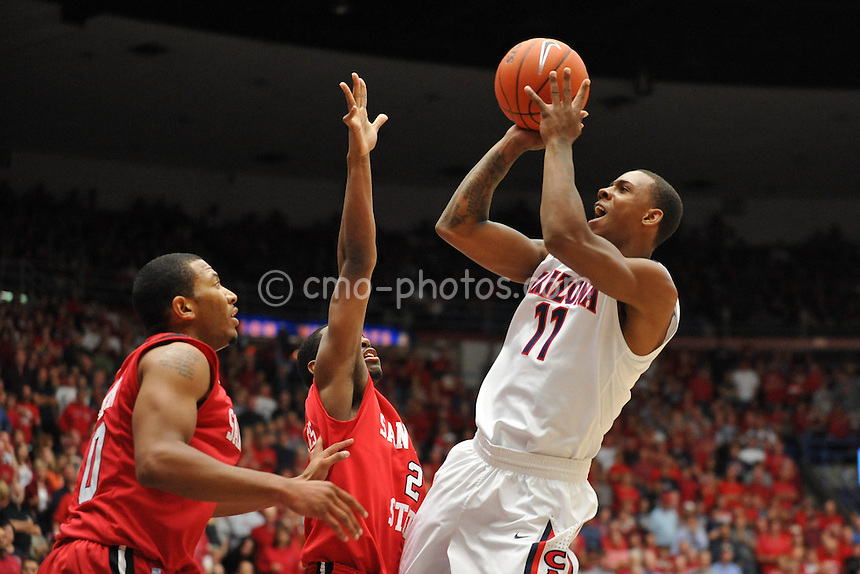 Nov 23, 2011; Tucson, AZ, USA; Arizona Wildcats guard Josiah Turner (11) shoots the ball over two San Diego State Aztecs defenders in the first half of a game at the McKale Center.  Mandatory Credit: Chris Morrison-US PRESSWIRE