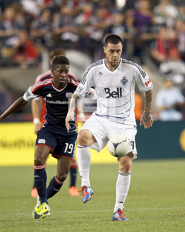 Vancouver Whitecaps FC forward Eric Hassli (29) passes the ball as New England Revolution midfielder Clyde Simms (19) closes. In a Major League Soccer (MLS) match, the New England Revolution defeated Vancouver Whitecaps FC, 4-1, at Gillette Stadium on May 12, 2012.