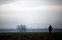 Pictured: A male migrants strolls in the mist with the barbed wire fence in the background Monday 07 March 2016<br /> Re: Refugees at the Greek FYRO Macedonian border in Idomeni, Greece.