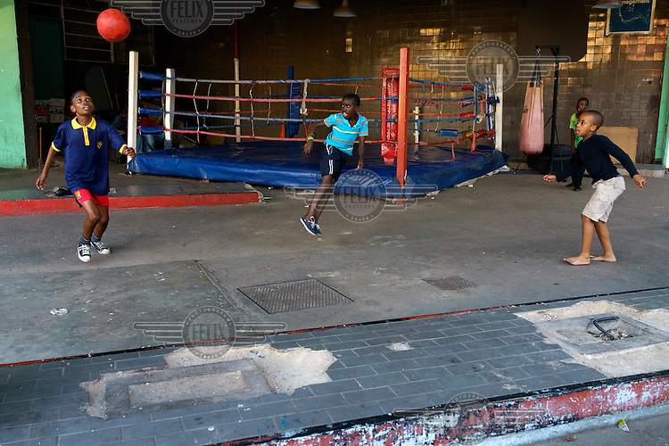 Children play football after finishing a boxing training session at the Hillbrow Boxing Club. After gunshot injuries put an end to his own boxing career, George Khosi founded the club to instil discipline, camaraderie and an activity away from the streets for young people from the community, and also to provide a training space for upcoming professional boxers. The club operates in a donated space on the forecourt of a disused petrol station in Hillbrow, one of the country's most notorious neighbourhoods.