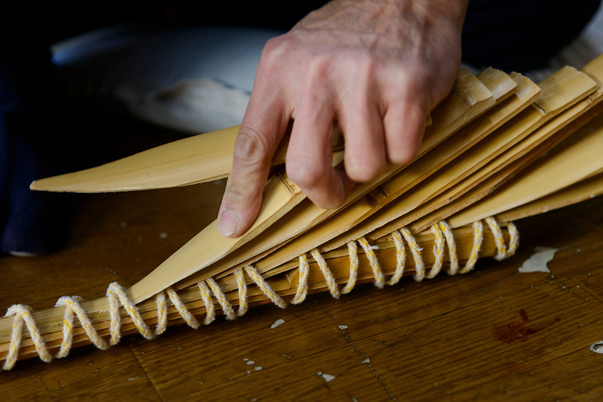 Reimei Yokoyama binding pieces of wood together for laminating as part of the bow making process. Wedges are used to keep the shape of the bow. Yokoyama Reimei Bowmakers, Miyakonojo, Miyazaki Prefecture, Japan, December 23, 2016. A handful of bowyers from the Kyushu city of Miyakonojo make over 90% of all the bows used in traditional Japanese archery. The bows are made from laminated bamboo and haze wood in process that consists of over 200 individual tasks. At over two meters from tip to tip the bows the longest used in the world.
