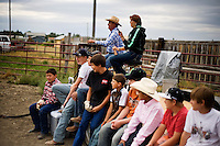 Young riders wait their turn on the mechanical bull at the Mechanical Bull-A-Rama at the Whoa Arena in Valier, Montana, USA.  The event, organized by Janelle Nelson, was a benefit for local youth rodeo participants and the local food bank.
