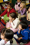 Education Elementary Grade 2 students listening in class sitting on rug vertical