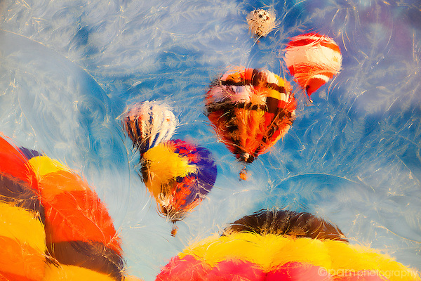 Colorful hot air balloons in the sky photographed under textured glass