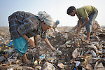 A poor family scavenges for recyclable items in the smoldering municipal garbage dump in Chennai, India.