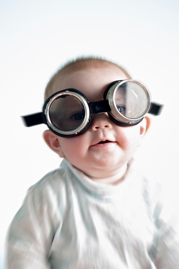 Portrait of 6 month old laughing baby girl wearing welders goggles over eyes