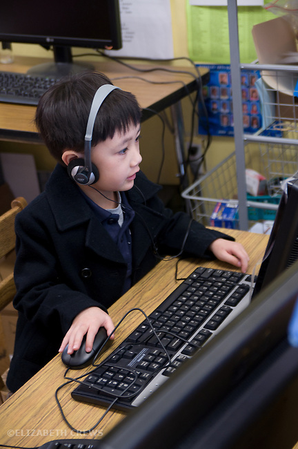 Berkeley CA Kindergarten student.Chinese American, learning via computers in class