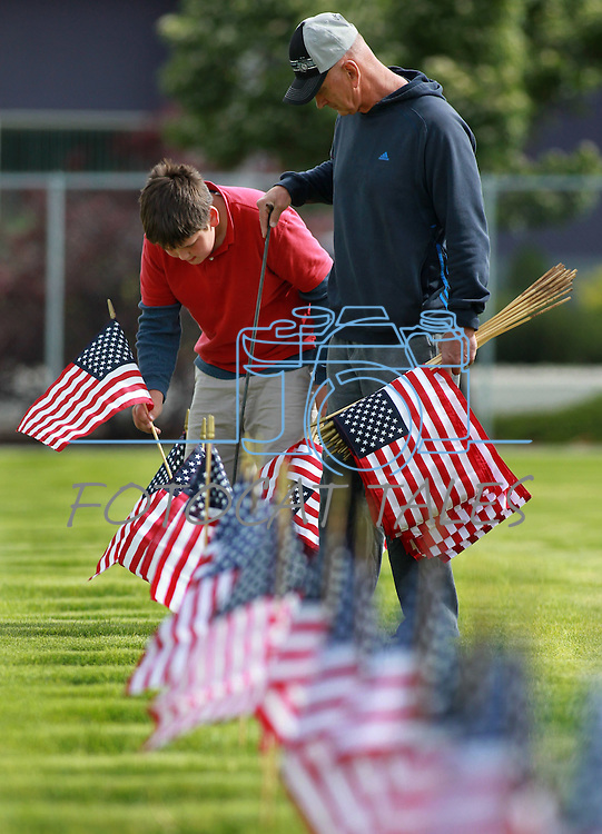 Volunteers Tyler Baker, 9, and his dad Wayne place flags on the graves of veterans at the Lone Mountain Cemetery in Carson City, Nev., on Friday, May 25, 2012. More than 1,400 flags were placed in honor of Memorial Day..Photo by Cathleen Allison