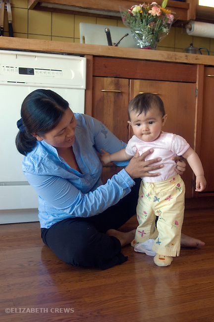 Berkeley CA Nepalese mother helping daughter seven-months-old stand up  MR