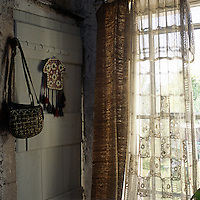 A bag hangs next to a rustic painted door in the corner of a stone room. A sheer curtain and a textured curtain hang at a window.