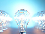 Closeup of lit up incandescent light bulbs on bright blue background. Power consumption concept.