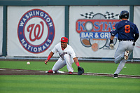 Auburn Doubledays first baseman Adalberto Carrillo (8) stretches for a throw as Corey Joyce (8) runs up the base line during a NY-Penn League game against the Connecticut Tigers on July 12, 2019 at Falcon Park in Auburn, New York.  Auburn defeated Connecticut 7-5.  (Mike Janes/Four Seam Images)