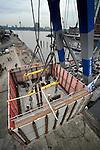 ROTTERDAM - In het centrum van Rotterdam hebben twee drijvende bokken een 500 ton zware, door Colijn Aannemersbedrijf gebouwde basculekelder opgehezen voor de nieuwe Rijnhavenbrug. De betonnen kolos is in het water op stalen buizen geplaatst waar het de basis gaat vormen voor de stalen brug over de Rijnhaven naar de Wilhelminapier. De 160 meter lange oeververbinding die in opdracht van de gemeente Rotterdam wordt gebouwd, zal wellicht een drukke stalen flaneerroute over het water worden, en kent in het midden een opvallend vormgegeven brugdek. De basculekelde komt te rusten op zes stalen funderings buispalen van 32 meter lang. COPYRIGHT TON BORSBOOM