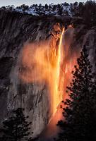 Sun illuminates Horsetail Falls at sunset. Yosemite National Park, CA